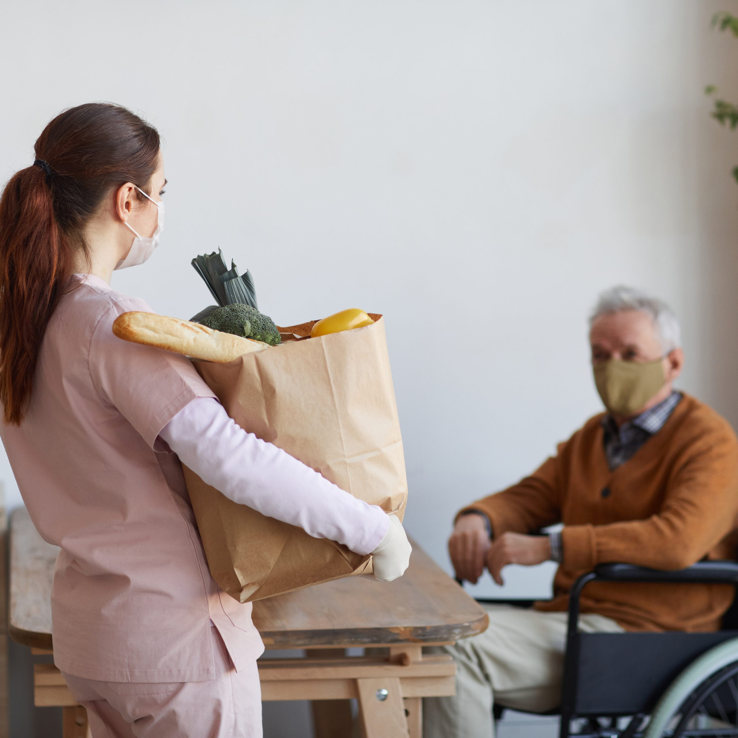 Caregiver delivery groceries to man