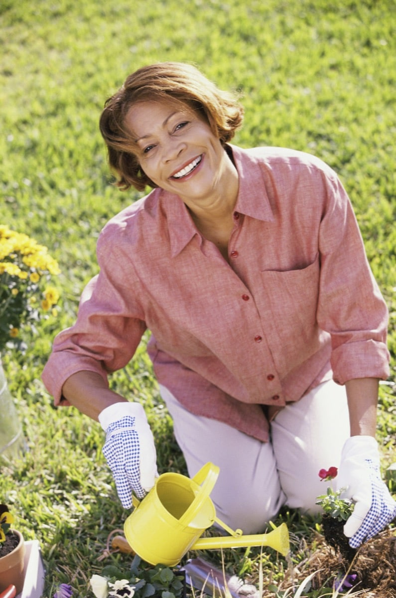 Senior woman gardening holding a watering can